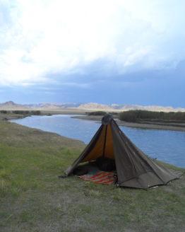 oilskin shelter on a flat landscape by a slow river