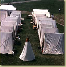 Two rows of small tents with a bell tent in the center
