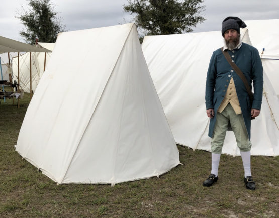 man standing next to the back of a tent