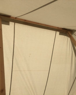 inside a white canvas tent looking up at wooden poles