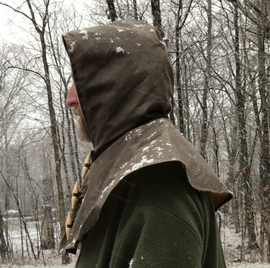 Profile view of a man wearing a brown oilskin hood