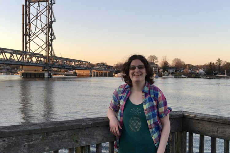 woman on pier with bridge in background